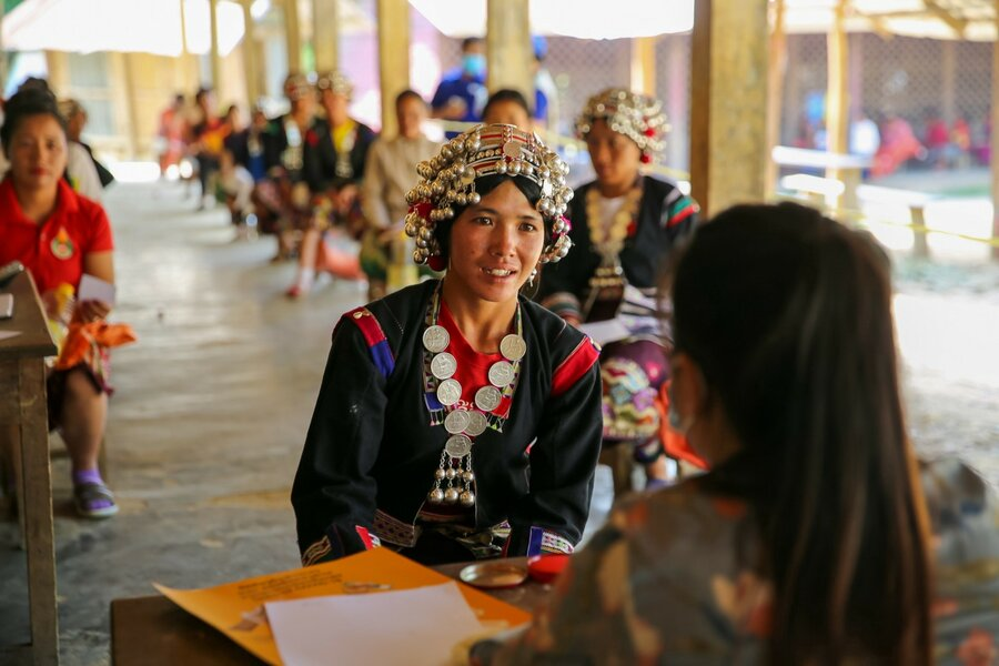 Member of the Akha community sitting at a small table speaking with WFP worker. Community members are wearing head pieces and traditional attire.