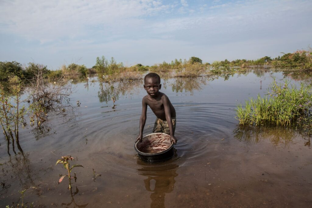 A boy washes a saucepan in the flood waters of Aweil - a town in the north of South Sudan.