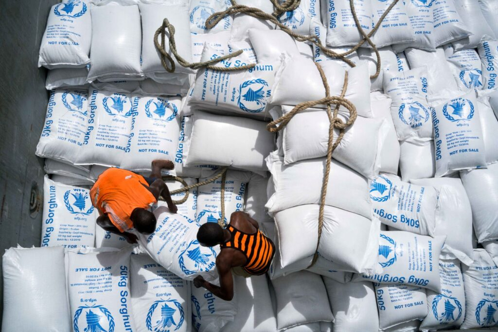 Porters loading WFP food bags onto cargo ship.