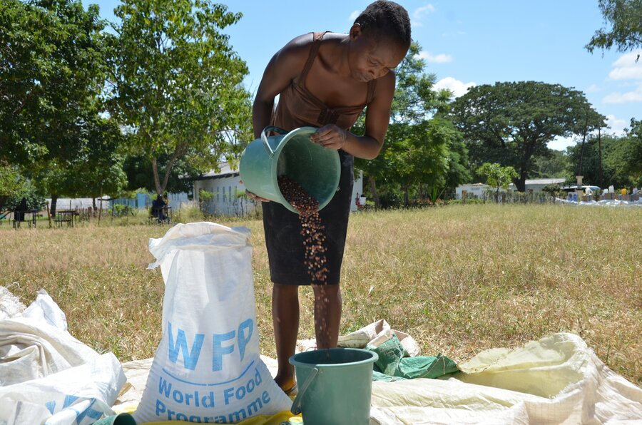 Woman from Zimbabwe is standing while pouring WFP grain from a green bucket into another green bucket.