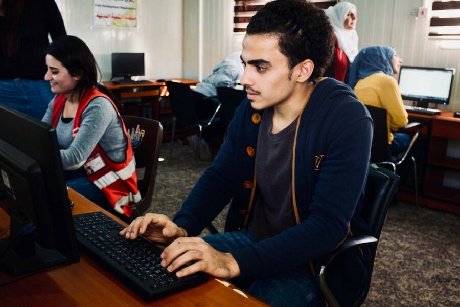 A young man sits at a computer, typing.