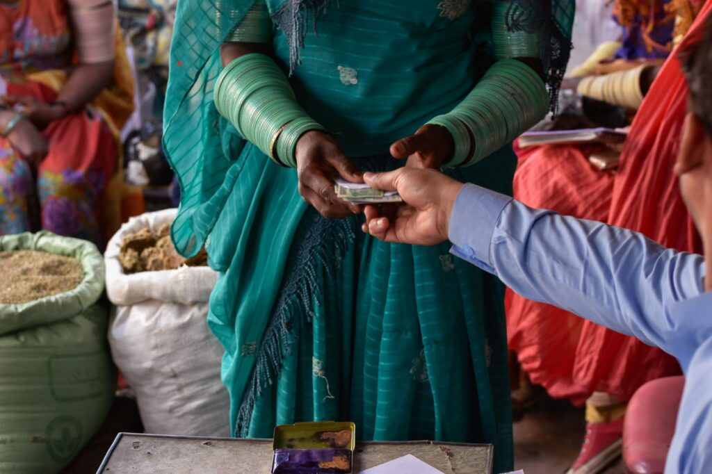 A woman in a green sari handles cash.