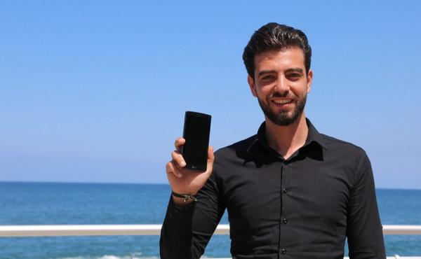 a young man holds up his phone at the beach