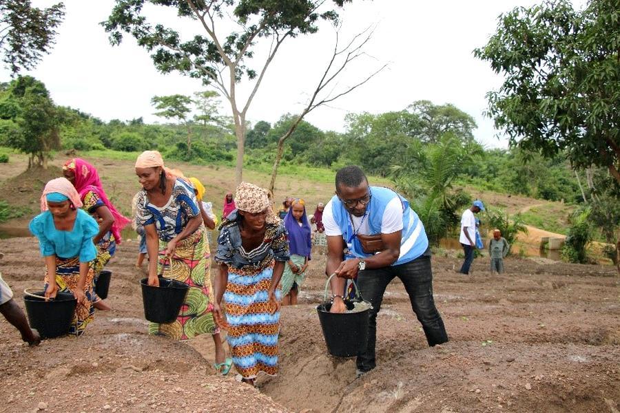A UN volunteer helps farmers plant food
