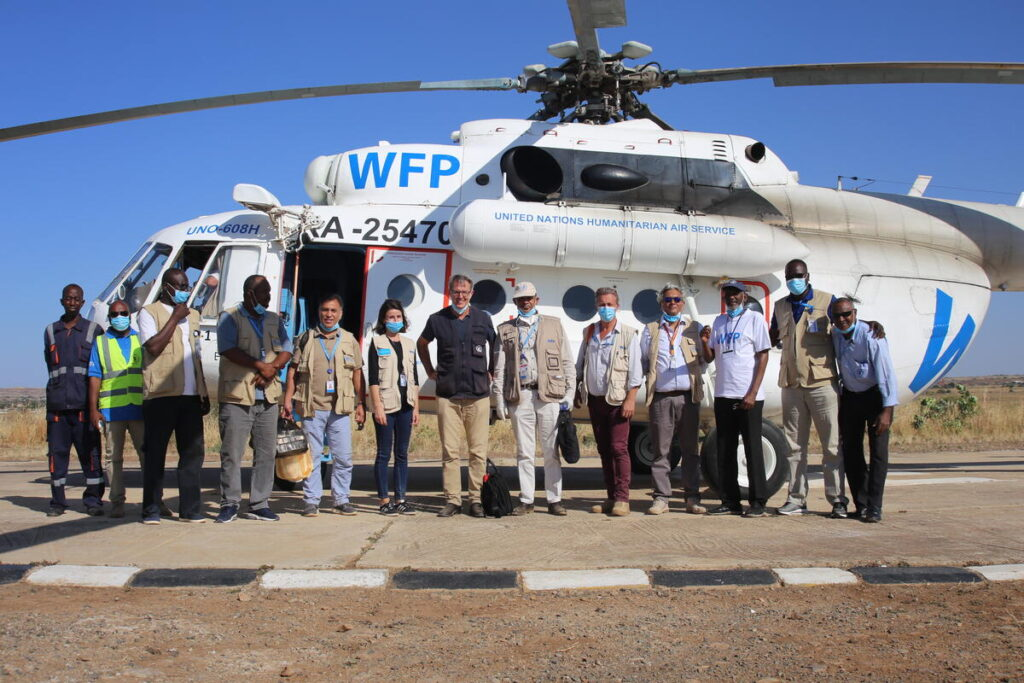 A group of WFP workers stand in a line in front of a transport helicopter.