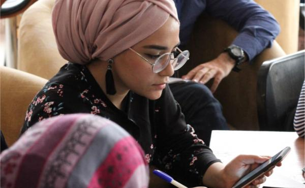 A woman in a headwrap looks down at her phone.