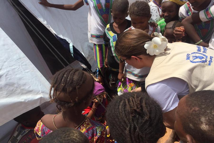 UN WFP volunteer hands out food to children in Mali