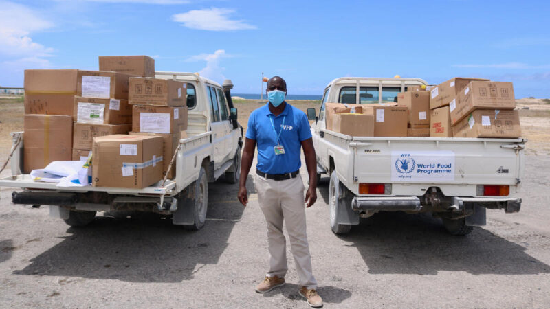 A WFP staff member in a blue shirt stands between two pickup trucks full of donations.