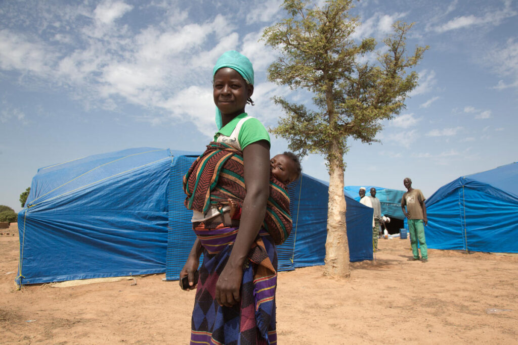 A woman stands outside of a refugee tent, her baby wrapped around her back with a cloth.