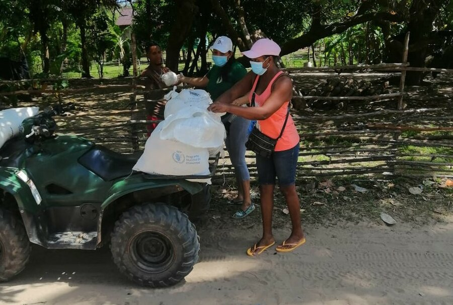 3 people in masks load a 4 wheeler with bags of food.