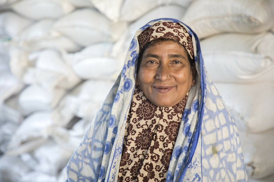 a woman in a head scarf smiles at the camera