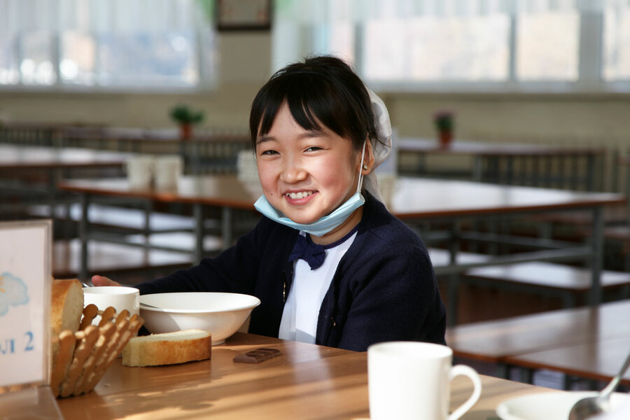A schoolgirl sits at a table to eat a meal, smiling, mask under her chin.