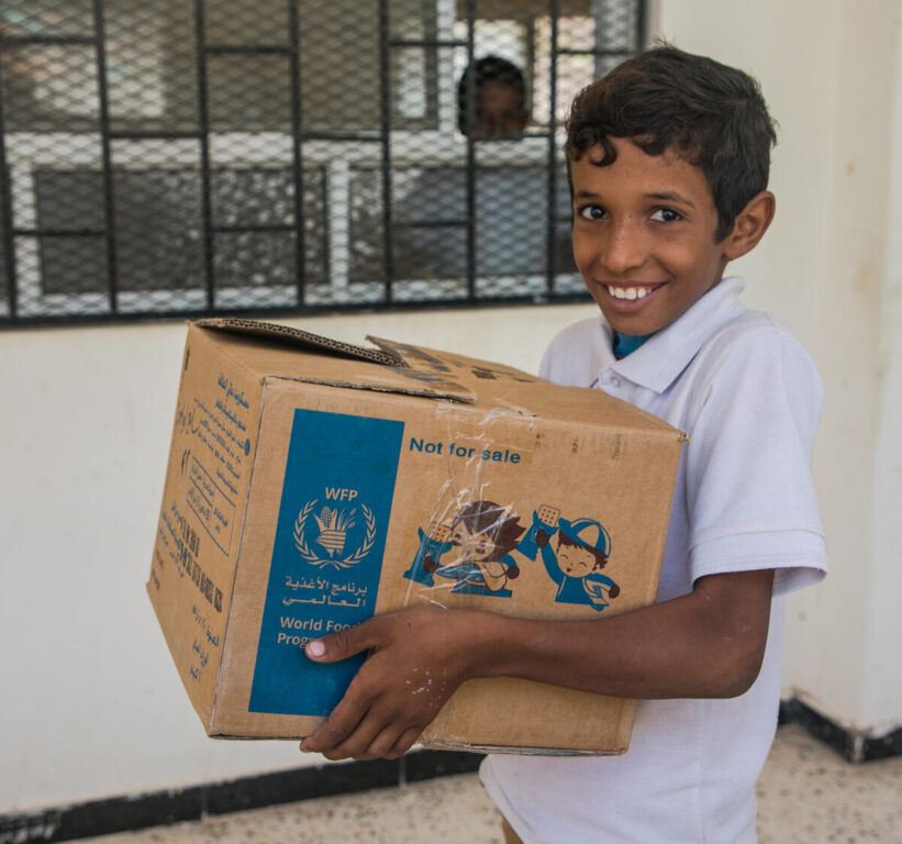 A schoolboy holds a box of WFP biscuits, smiling.
