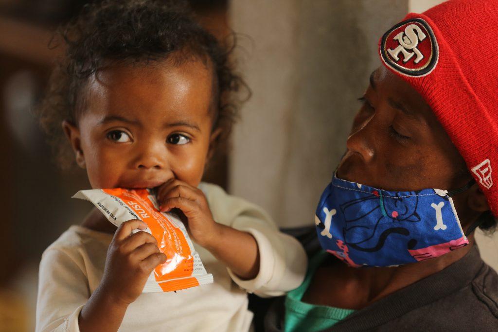 a little girl eats WFP nutrition bar