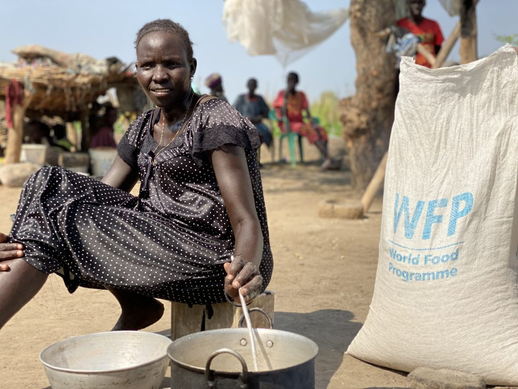 a woman stirs food in a pot