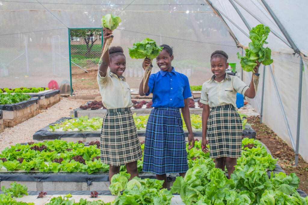 Three young women hold up veggies, standing in a garden.