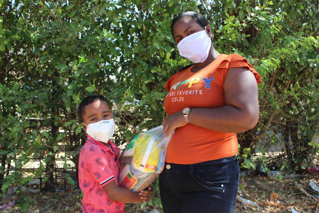 A mother and daughter in masks hold a bag of food.
