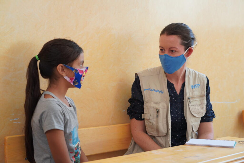 A WFP staff member speaks with a schoolgirl in a mask.