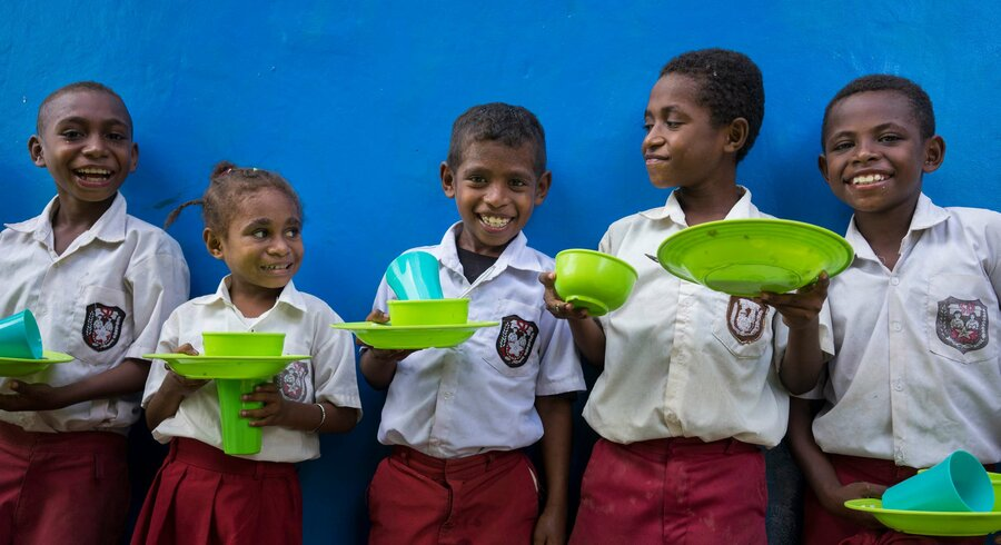 5 schoolkids pose in front of a blue wall, holding green plates and cups.