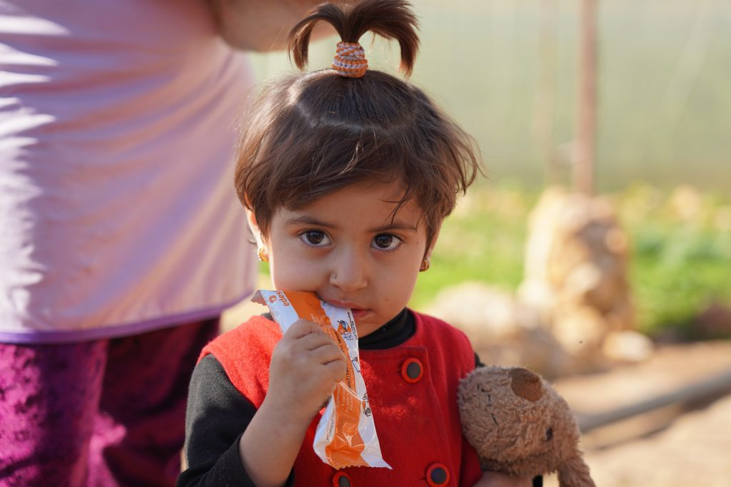 a young girl takes bite of nutrition bar