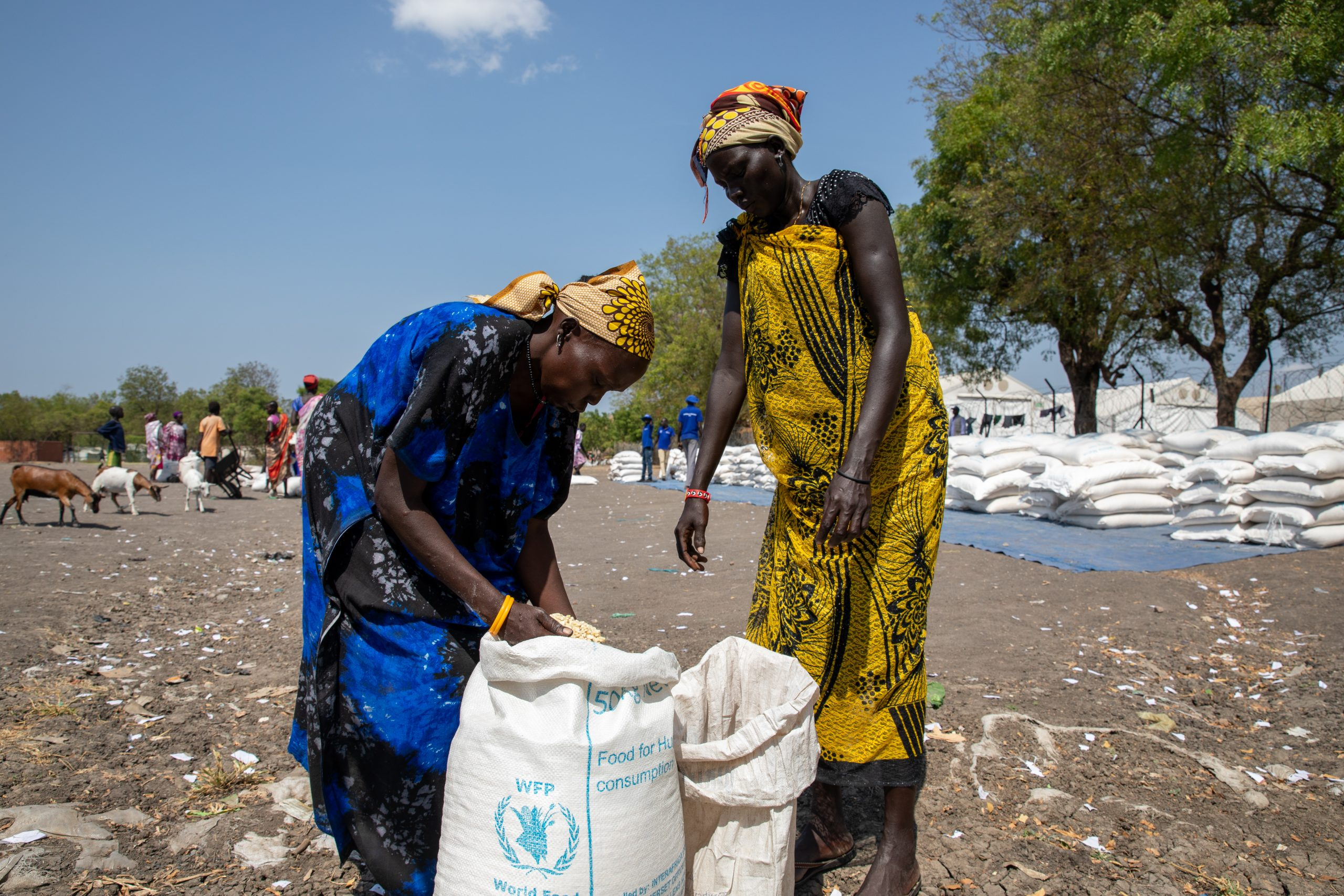 two women bend over WFP bags of food