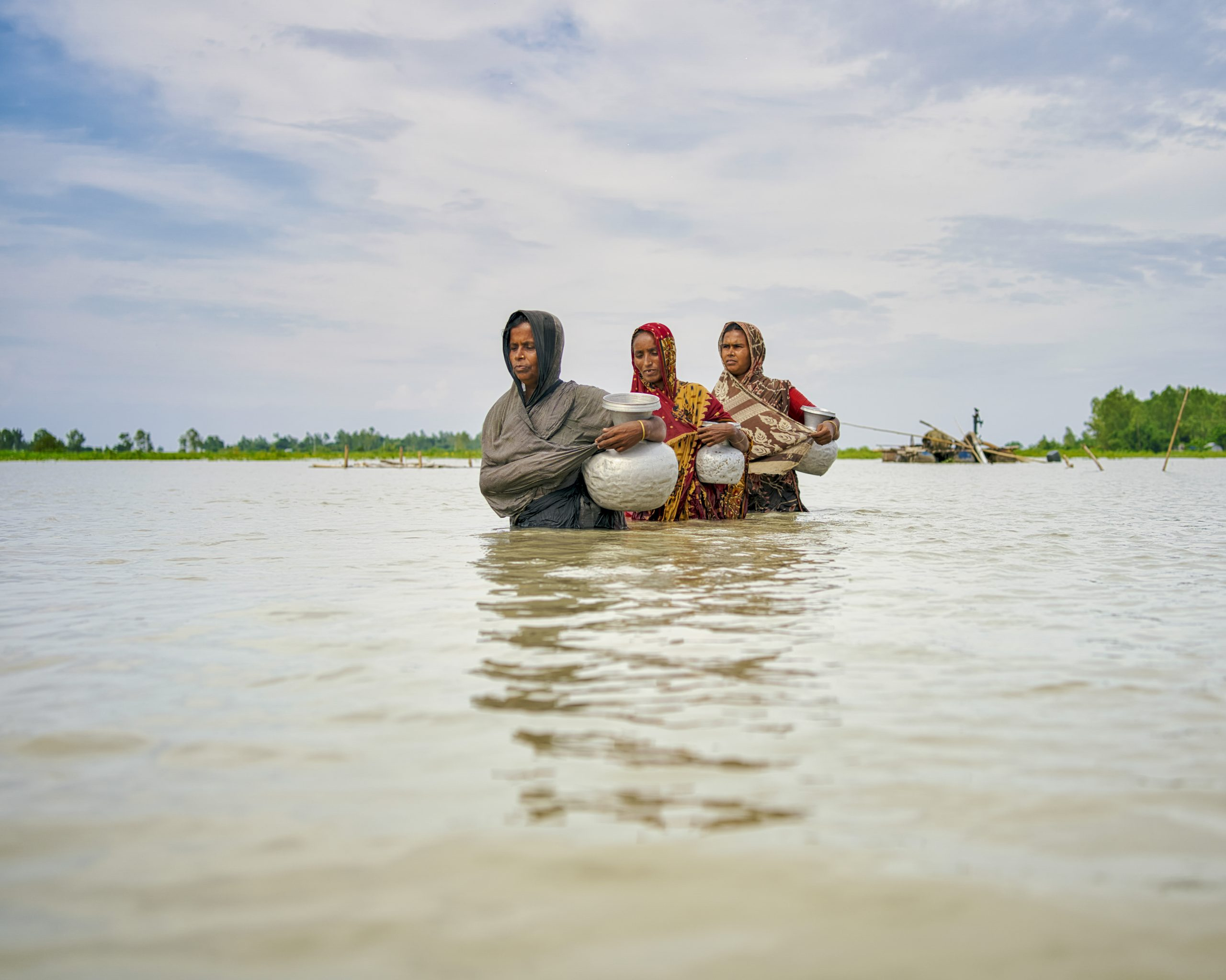 women wade through water carrying bowls of food
