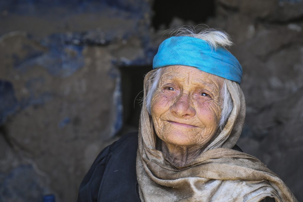a woman in blue and grey headscarf smiles