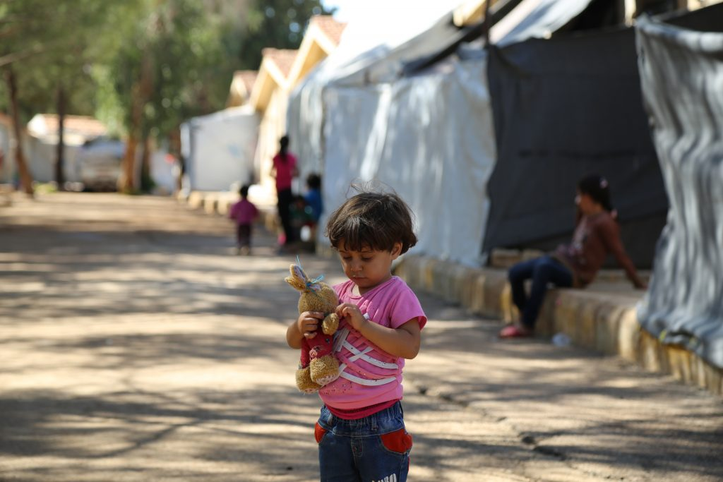 a young girl holds a stuffed animal