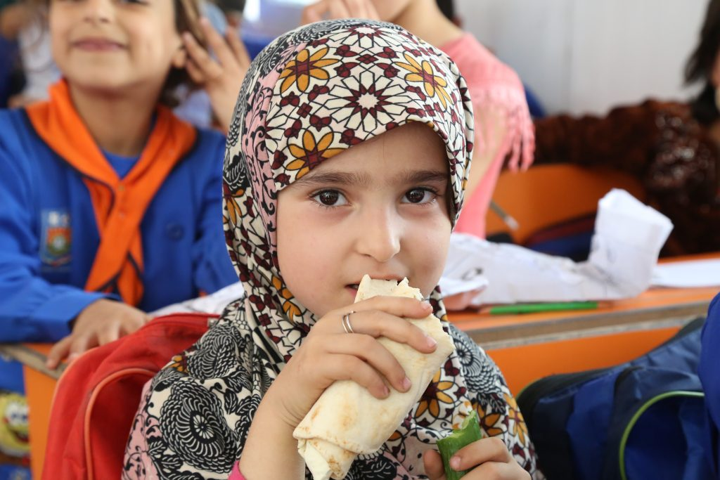 a young girl in colorful headscarf bites sandwich