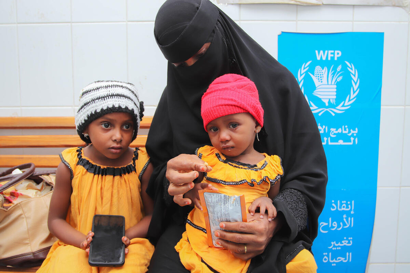 a mother in full headscarf and dress holds her daughters