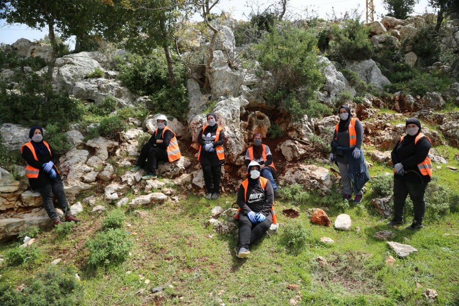 group of people in orange vests in forest