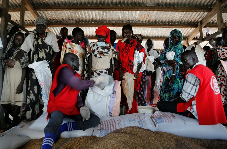 refugees sort through bags of food