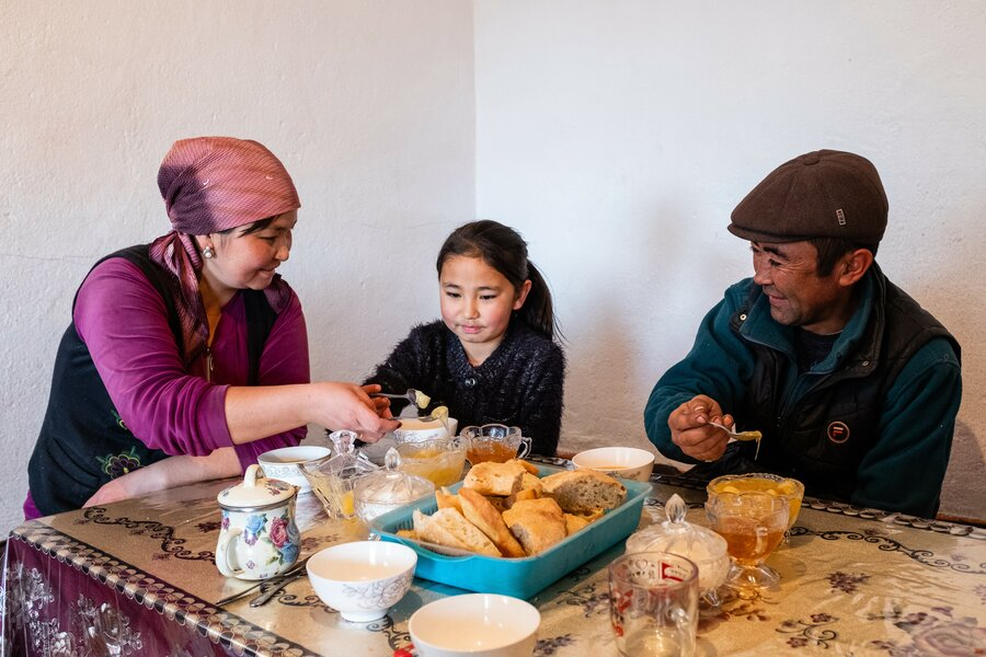 family gathers around table of food