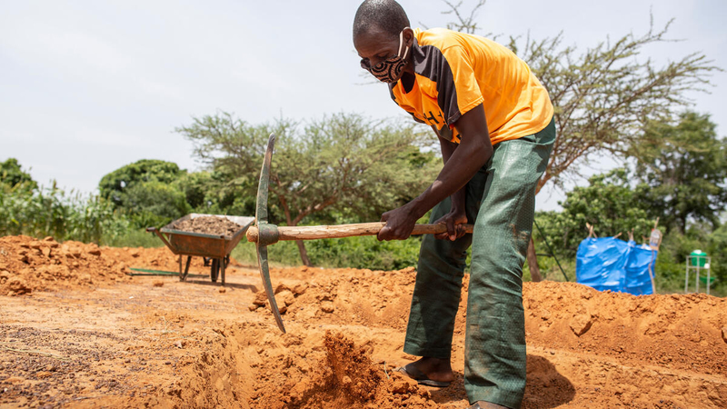 man farms with tool