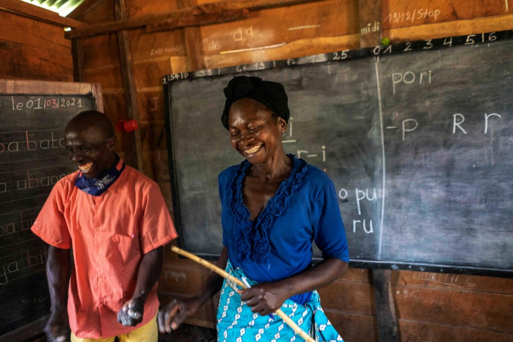 A woman smiles, standing next to a tutor in front of a chalkboard.