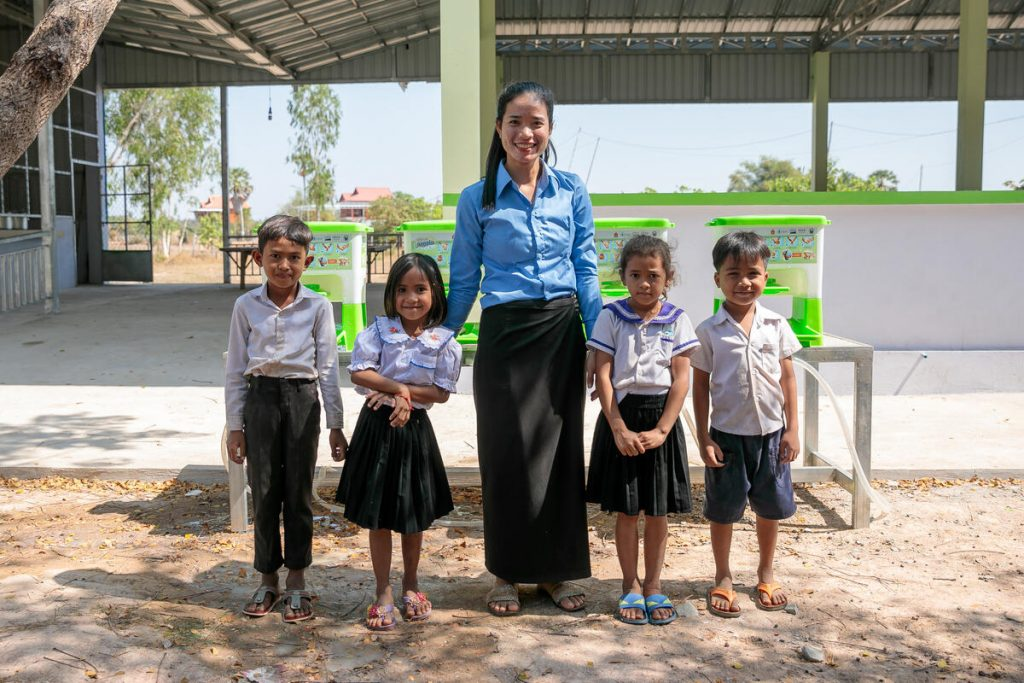 A teacher smiles, standing with four young students.