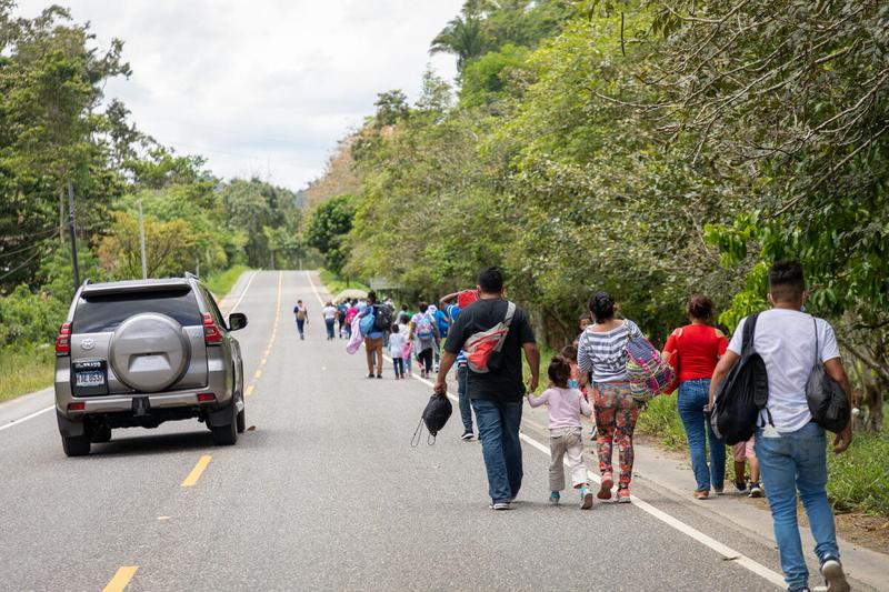 migrants walk on road