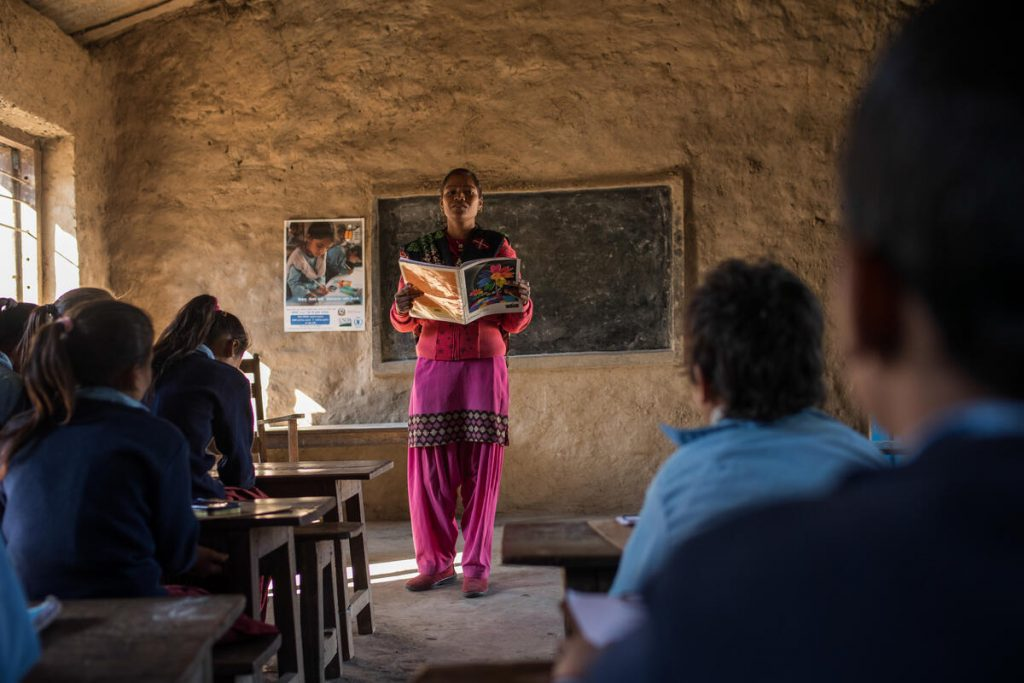 A teacher stands in front of a classroom of students, reading from a book.