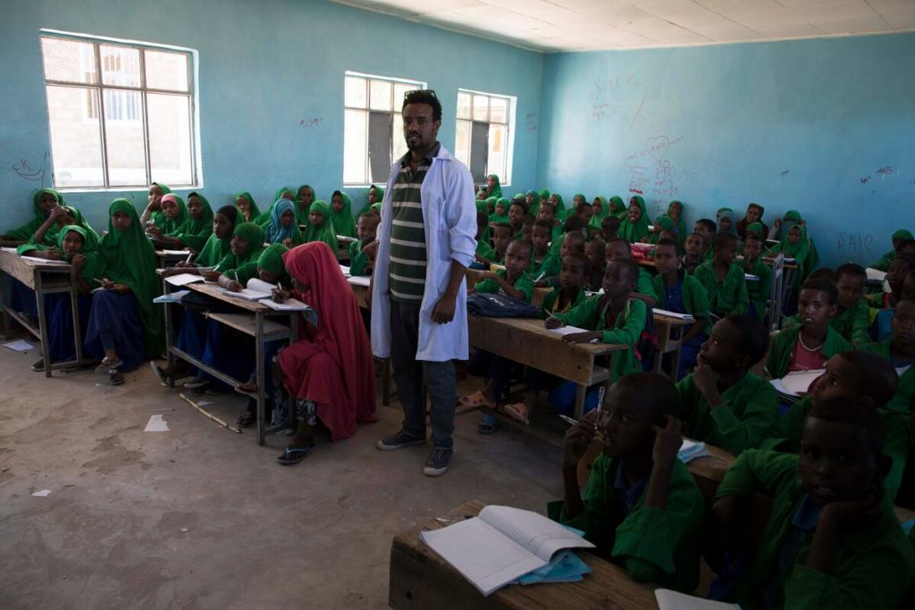 A teacher in a white coat stands in front of a classroom of students in green uniforms.