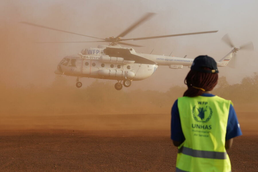 helicopter taking off in dusty field