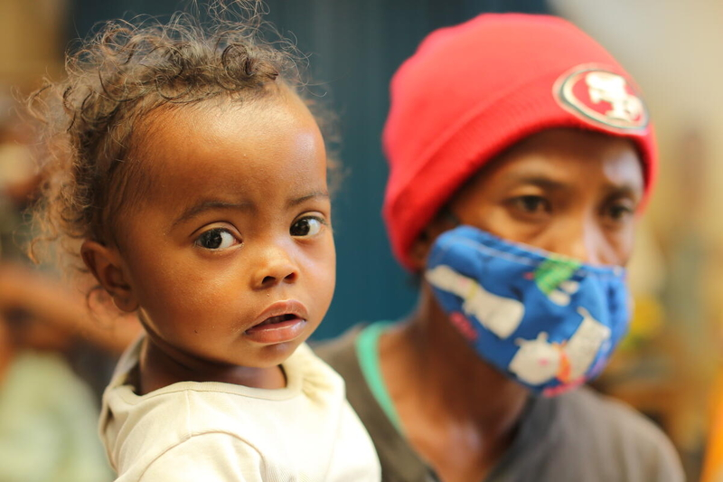 mother in covid health mask holds her daughter