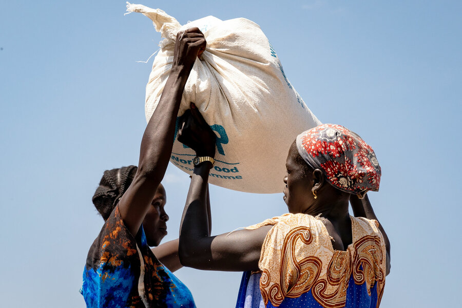 two woman lift a WFP bag of food