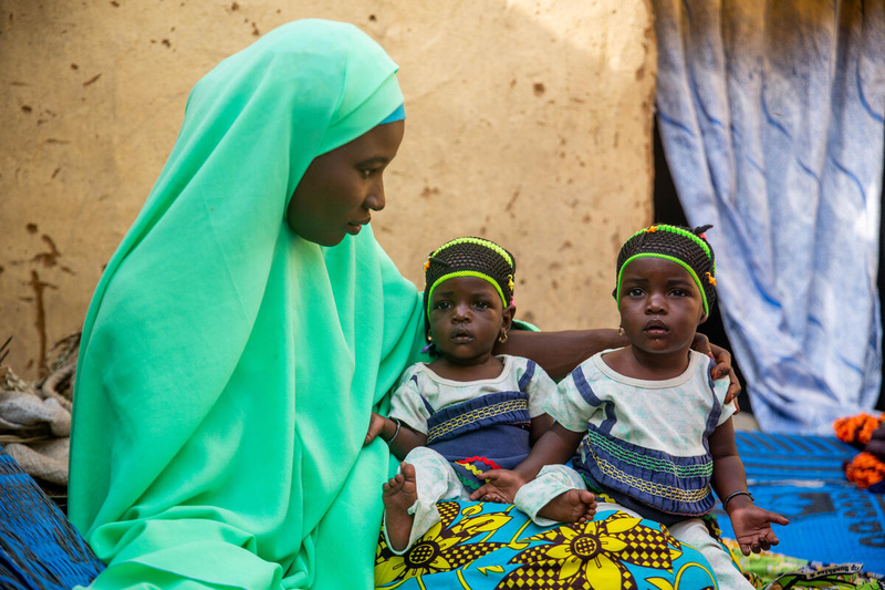 Mother and 2 children sitting in Nigeria, where famine is causing children to be malnourished