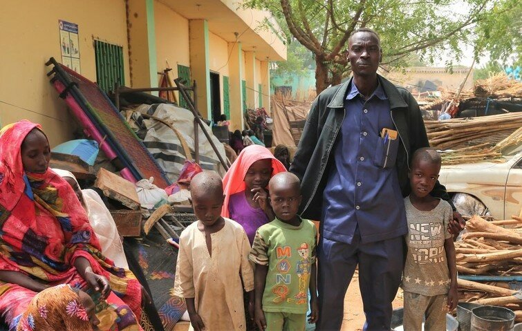 man stands with his family in front of building
