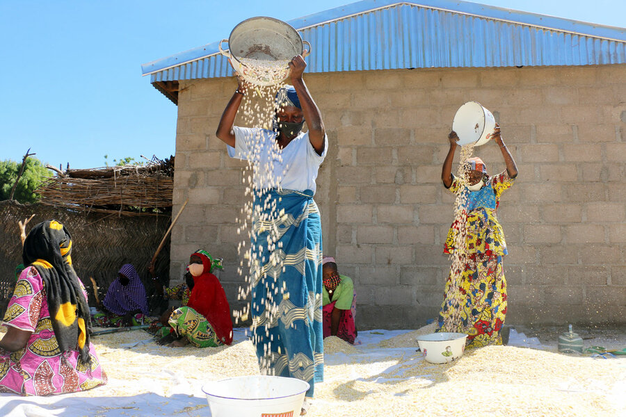women in colorful skirts sifting food
