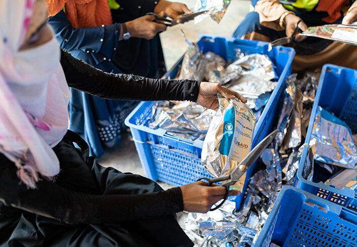 Rohingya woman sorts through UN WFP packaging in Cox's Bazar refugee camp in Bangladesh