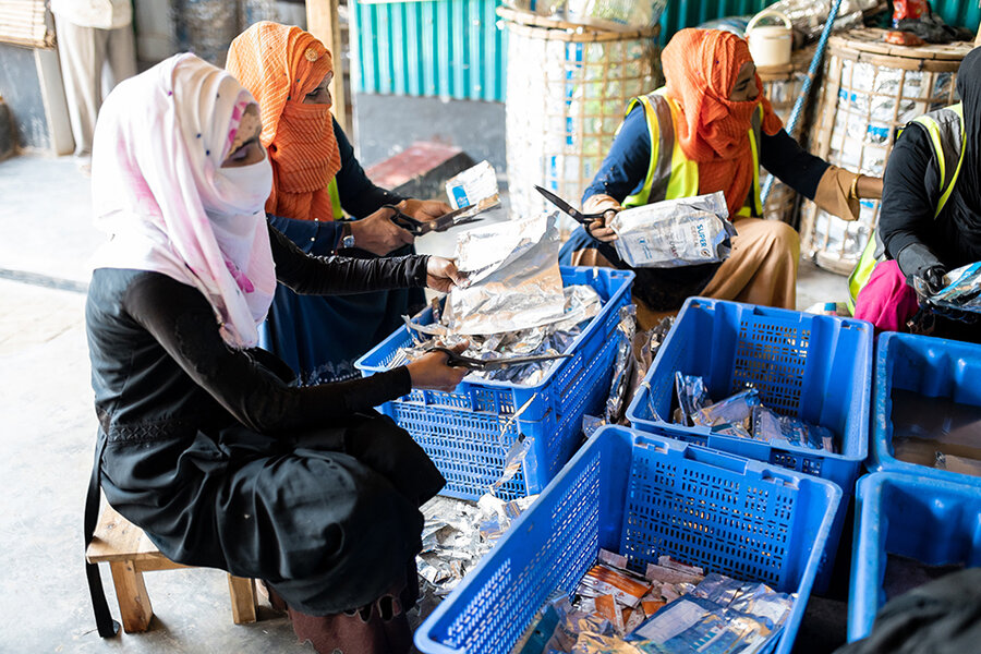 Women sort plastic and aluminum packaging at UN WFP's Upcycling center in Cox's Bazar refugee camp, Bangladesh