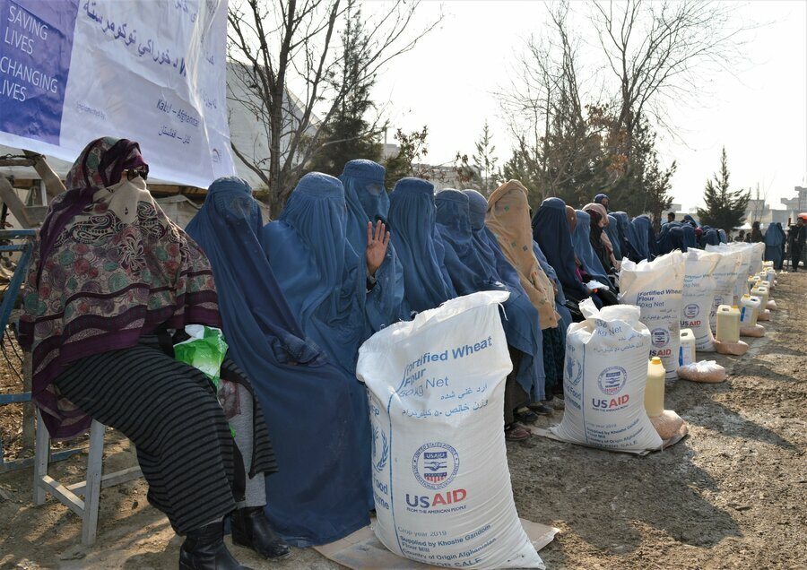 women in burqas sitting next to bags of food