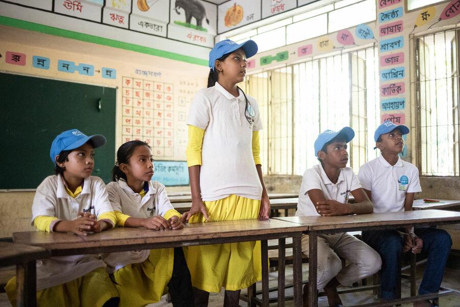 schoolchildren in white and yellow uniforms in class