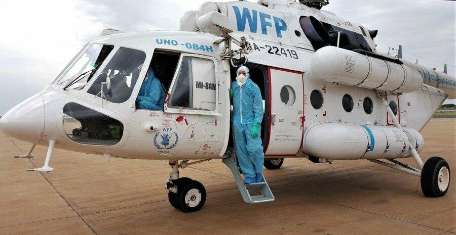 WFP worker stands in door of helicopter wearing PPE